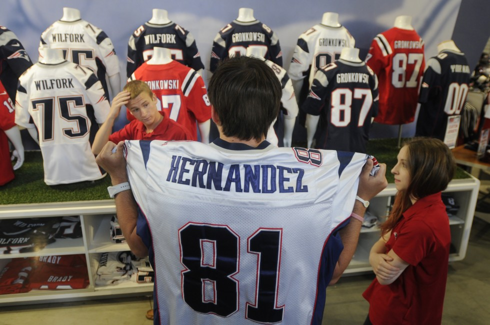 Andrew Lucas, of New Bedford, Mass., right, talks to sales associates in the New England Patriots Pro Shop at Gillete Stadium, about replacing his Aaron Hernandez jersey. He was undecided if he would trade in the jersey because he is also a University of Florida fan, and wanted to make sure he could get a same values shirt, $250, in a player he wanted.