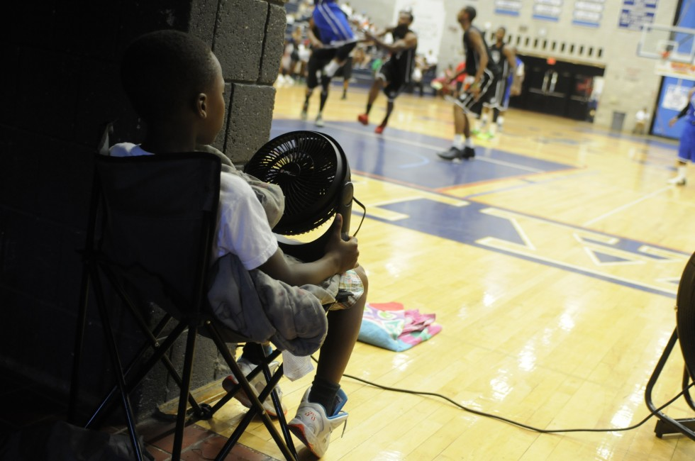 Trying to keep cool in a warm gym, Damnic Gittens, 7, of Hartford, puts a fan his mother brought to the game to good use. His mother works for the Greater Hartford Pro-Am, and he and his brother help earlier with setting up for tonights event.