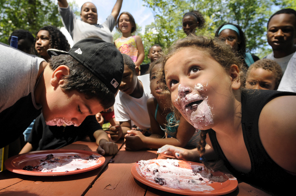 "2013/07/30 Durham - Lizbeth Velez, 8, of New Haven, (right) glances up at camp counselor Melissa Mathews (off camera) to see if she has won a ""pie"" eating contest during the Farnam Olympics at Camp Farnam in Durham Tuesday morning. Her opponent, Alexis Hernandez, 12, (left) of Hamden, was ultimately declared the winner.  The ""pie"" consisted of a mound of Marshmallow Fluff, jelly and sprinkles."