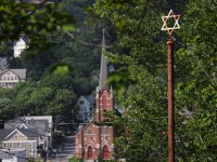 A star of David, which stands on a pole at the entry way to Holy Land, is visible from the grounds.