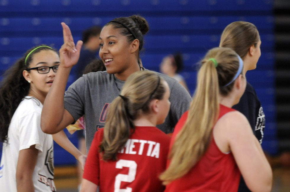 UConn basketball player, Kaleena Mosqueda-Lewis breaks up a huddle while coaching at the Kara Wolters Dream Big Basketball Camp for girls at Avon High School.