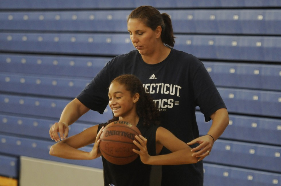 Former UConn basketball player Kara Wolters plays defense as she coaches Corina Lindsay, 15, of Longmeadow, Mass., on an inside move during the Kara Wolters Dream Big Basketball Camp for girls held at Avon High School.