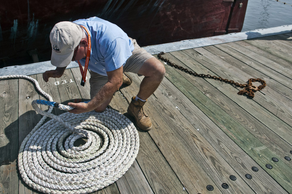 2013.07.21 - Mystic, CT - As the Charles W. Morgan is set afloat and her ropes loosen, Robert Long of Mystic Seaport coils the slack. Photograph by Mark Mirko | mmirko@courant.com