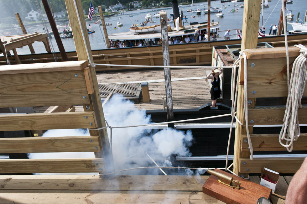 2013.07.21 - Mystic, CT - Artist April Kelly, of New York, covers her ears on the deck of the Charles W. Morgan as a tiny canon is fired to signal the Charles W. Morgan has been set afloat. Photograph by Mark Mirko | mmirko@courant.com
