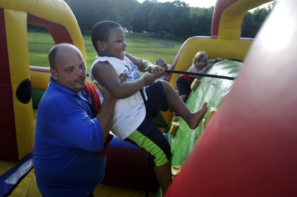 Philip Patton, of West Haven helps Keyion Davis, 6, of Hartford, over a an obstacle course. Patton works for D&A Amusements, out of Cheshire, and was manning the booth when Davis needed a lift.