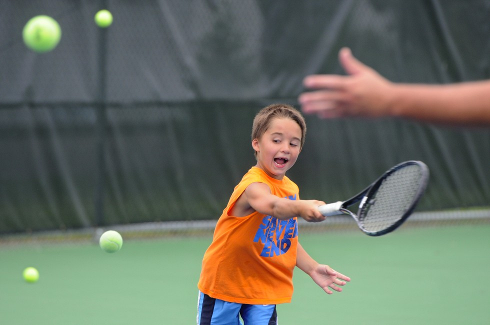 Joseph Nadau, 6, of Avon, hits a ball tossed by Alex Dahlem, 20, also of Avon, as balls from other players fly by.