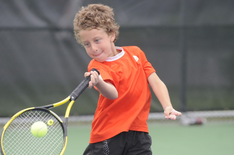 M.J. Chaho, 7, of Avon, hits a ball tossed by Alex Dahlem, 20, also of Avon.