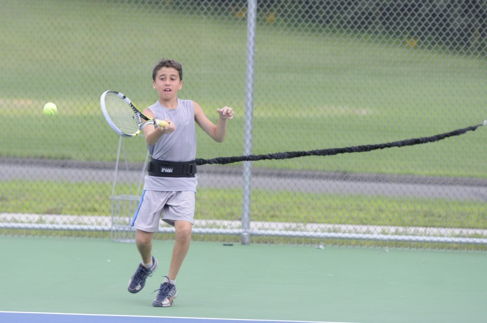 Alex Chaho, 10, of Avon, hits a ball tossed by Alex Dahlem, 20, also of Avon, while connected to a bungee chord. The chord is used for resistance and was combined with an x-drill to work on conditioning his legs.