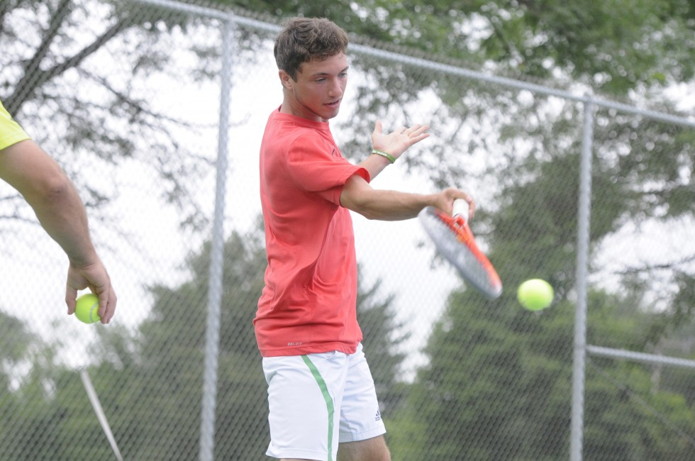 Evan Selzer, 18, of Avon, hits a ball tossed by Simsbury High School tennis coach Michael Chaho, also of Avon, during an informal practice and conditioning program Chaho is running this week on the tennis courts of Avon Middle School.