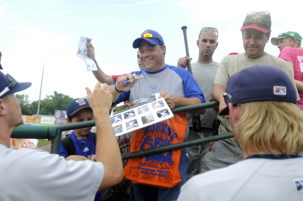 Elliott Cohen, of Woodmere New york, smiles and he gets autographs from the minor leaguers before the game, along with his son, Joey, 7, to the right.