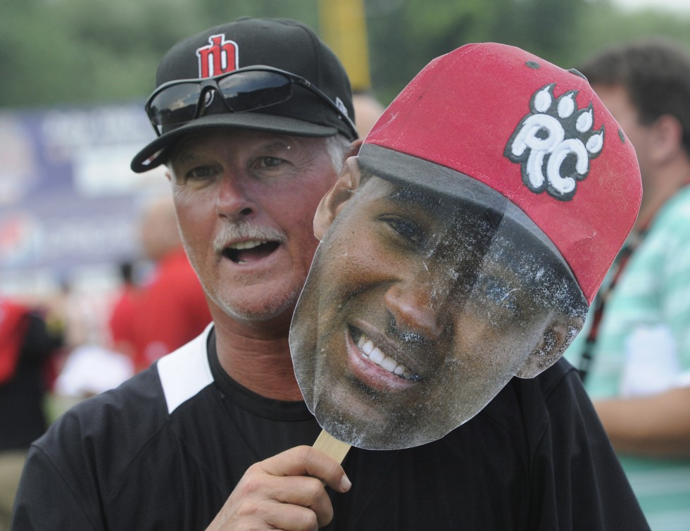 Rock Cats pitching coach, Stu Cliburn, holds a paper cutout of Rock Cats short stop Danny Santana which was handed to fans as they entered the ballpark.