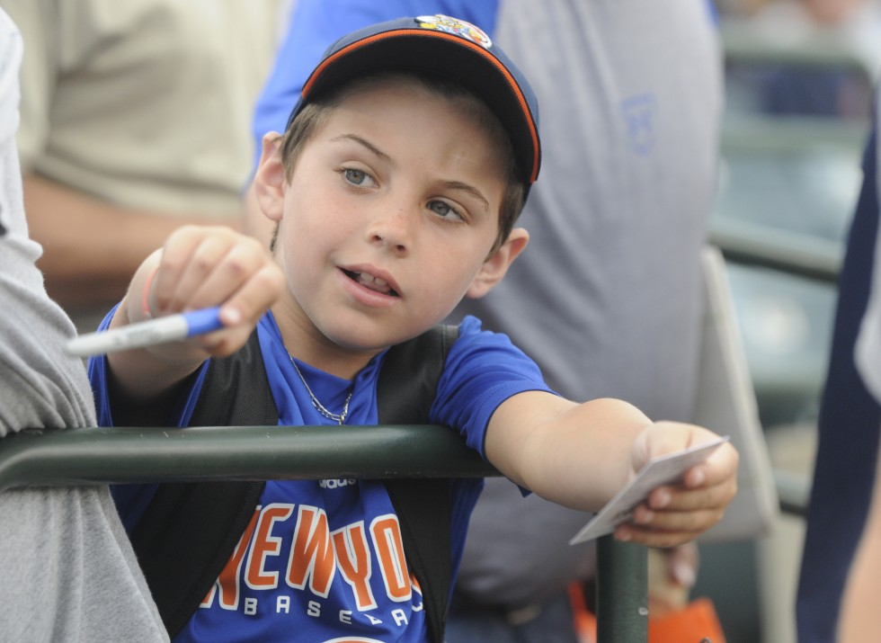 Joey Cohen, 7, of Woodmere, New York,  reaches to get a player to sign an autograph.