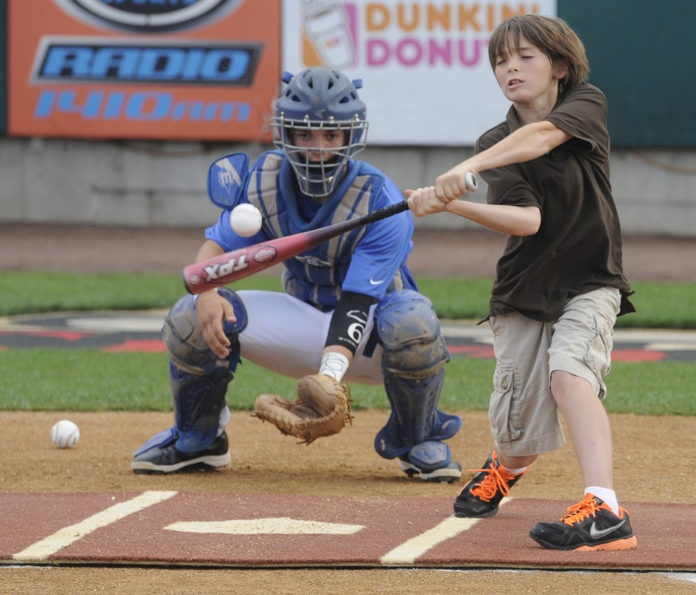JoJo Solomon, 10, of Sudbury, Mass., hits one of the first pitches to open the game as Cody Charneski, a catcher for Plainville High School catches. JoJo's family are the owners of the Rock Cats.