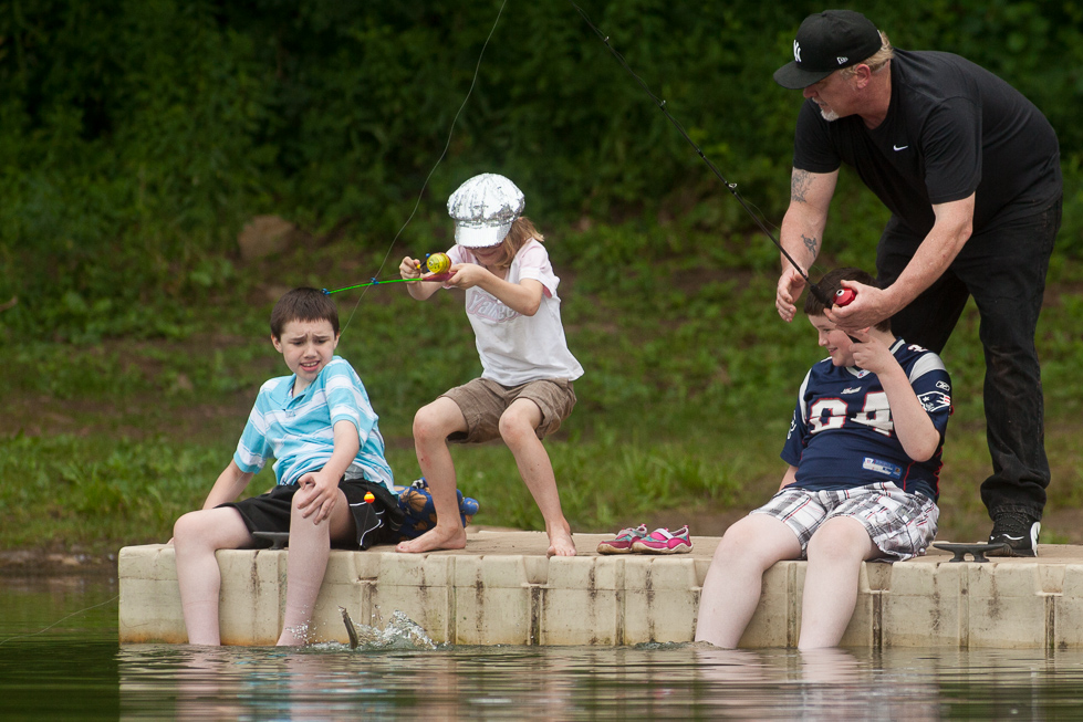 "2013.07.28 - Southington, CT - Jesse Freeman (left), 10, James Freeman, 9, and the boys' father Don Freeman react to their sister Emilee Hinton, 8, of Southington catching a fish at Crescent Lake on Sunday. The two brothers have Duchenne muscular dystrophy, a degenerative genetic condition that leaves them unable to walk, but were able to use their motorized wheelchairs at the lake. ""I love this dock because you can drive (a wheelchair) right out,"" said Brian Hinton, the boys' stepfather. In April, the family held an event at their church to help raise money for a van with a wheelchair lift. Hinton says their van came just in time, as James lost the ability to walk just a few months ago. Photograph by Will Parson 