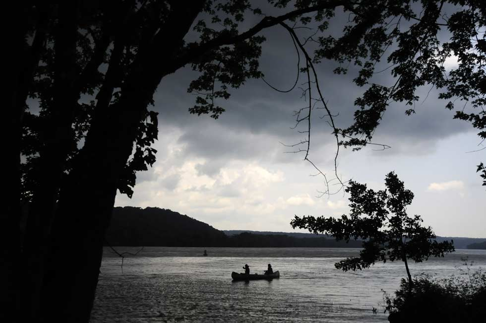 Canoeists paddle to shore to take cover before a storm at Haddam Meadows State Park Tuesday morning. The 13 campers from Incarnation camp in Ivoryton were taking part in a three day canoe trip down the Connecticut River from Middletown to Essex when the storm interrupted their journey.
