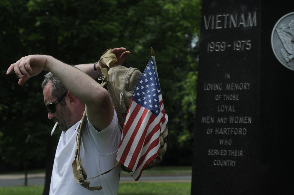 Welintukonis puts his backpack back on after a break at a Vietnam memorial on New Britain Ave. in Hartford.