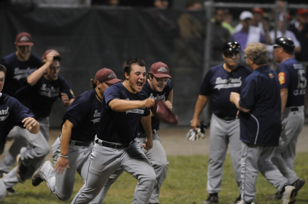 Branford players run from the dugout and onto the field to celebrate their victory for a second time after the umpires declared the game over.