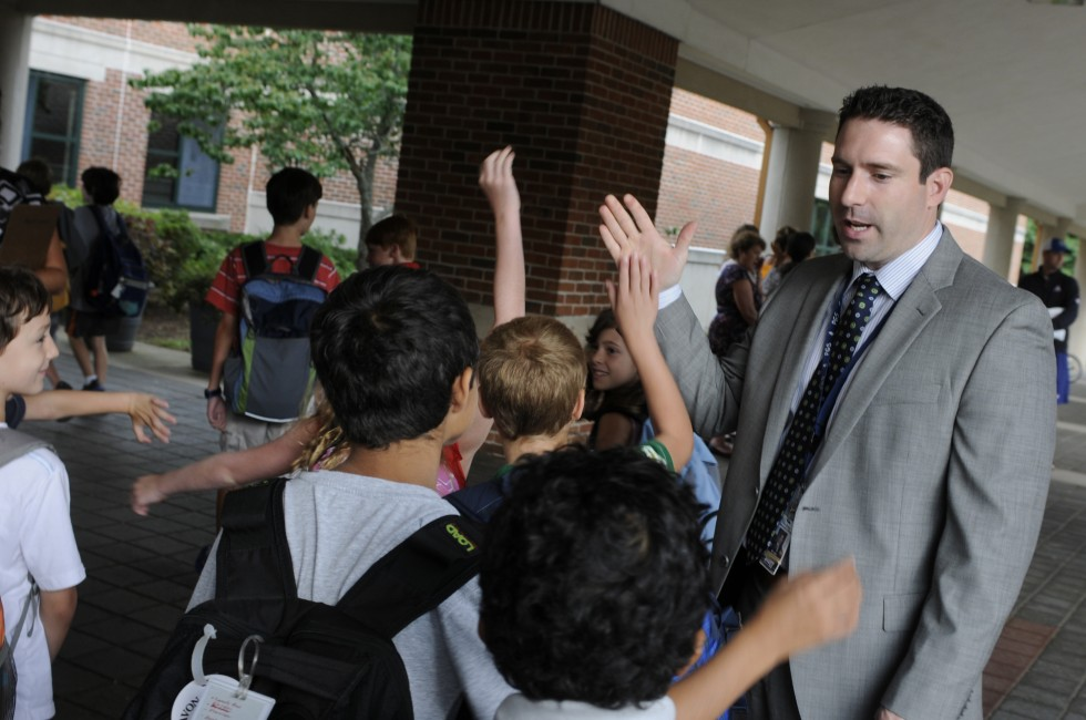 Jess Giannini, the new principal at Avon's Pine Grove Elementary School gives a group of fourth grade students high fives as they head into the school on their first day.