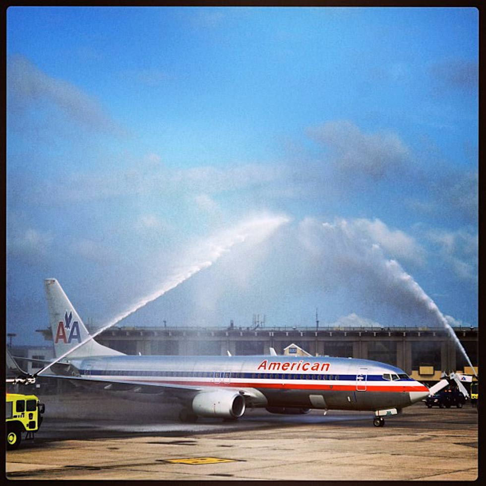 Bradley International Airport firefighters spray American Airlines flight 1353 with water canons to mark its inaugural non-stop flight to Los Angeles on August 27, 2013.