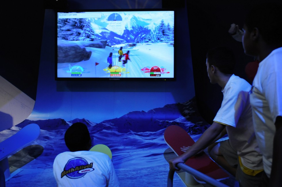 Children from the New Britain CPEP program play a game called BorderCross in the MathAlive! exhibit at the Science Center in Hartford. The game teaches angles and precision balance in the form of a ski race.