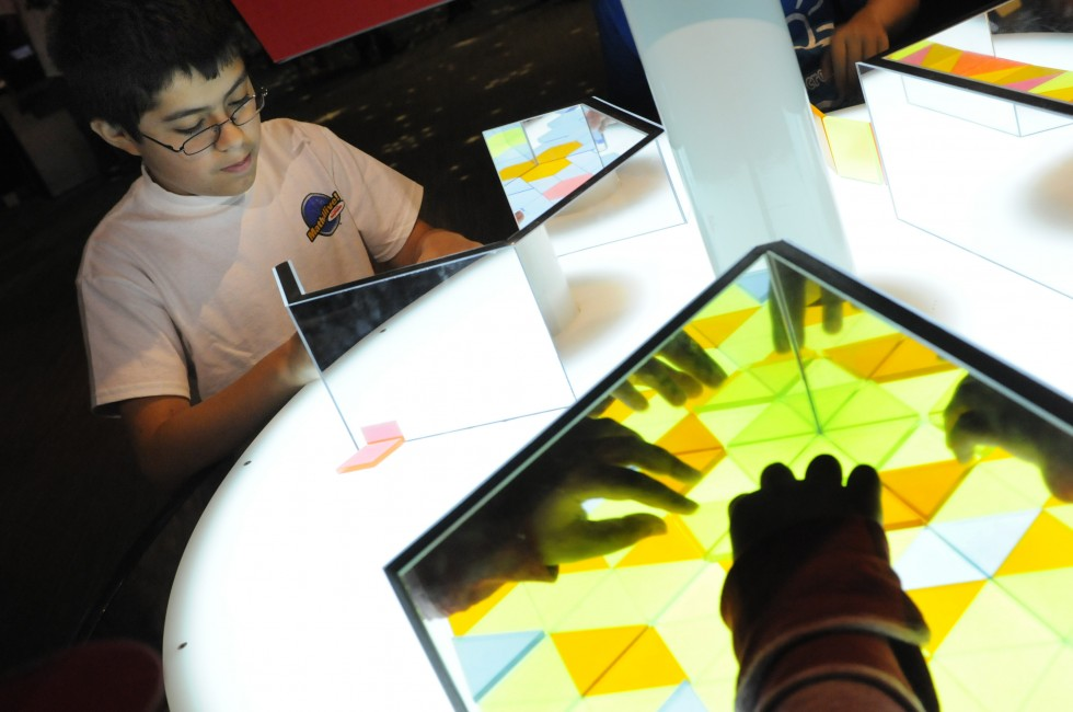 Alexis Diaz, 12, of Waterbury, who attends West Side Middle School, plays a game called, Tessellations, in which children are challenged to create patters that repeat  a game to create patterns that repeat in the MathAlive! exhibit at the Science Center in Hartford.