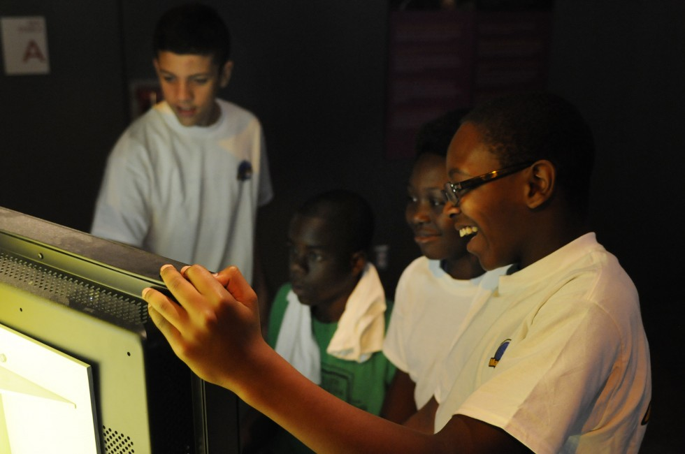 From left, Nathan Aviles, 13, Nosa Igbinewuare, 14, Kayin Bennett, 12, and Davonte Howard, 13, gather around a game in the MathAlive! exhibit at the Science Center in Hartford.