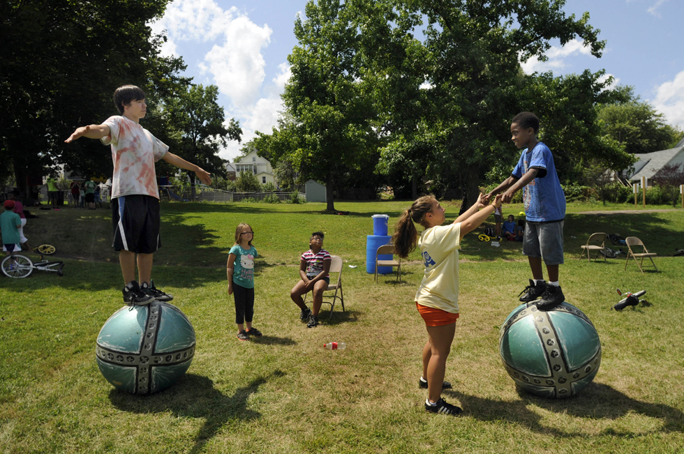 Counselor Regis O'Neill, 16, (left) shows camper Michael Burrill, 10, (right) how to balance on a rolling globe as Burrill gets a hand from counselor Micaela D'Antonio, 18.