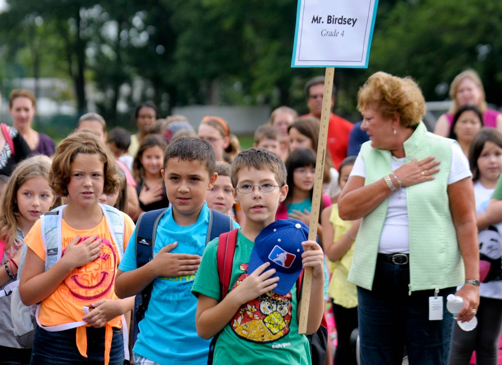 During the first day of school in Wethersfield, students, parents and staff recite the Pledge of Allegiance at 8am on at Charles Wright Elementary School. From left (with the smile face t-shirt) are fourth-graders Arianna Shink, 9, Mirnes Becirovic, 9, and Jimmie Clark, 9.