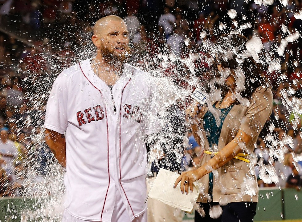 Jonny Gomes #5 of the Boston Red Sox, who knocked in the tying run in ninth inning, is doused with water as he is being interviewed after defeating the Seattle Mariners  at Fenway Park on August 1, 2013 in Boston, Massachusetts.