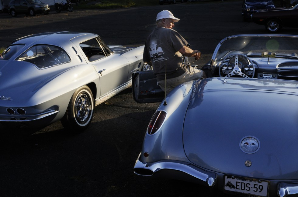 Ed Jolly, of Willington, gets into his 1959  Corvette at the conclusion of the cruise night, next to his wife's 1963 Corvette split window Stingray. The rare 1963 split window Stingray Corvette to his left, is owned and driven by Joly's wife.