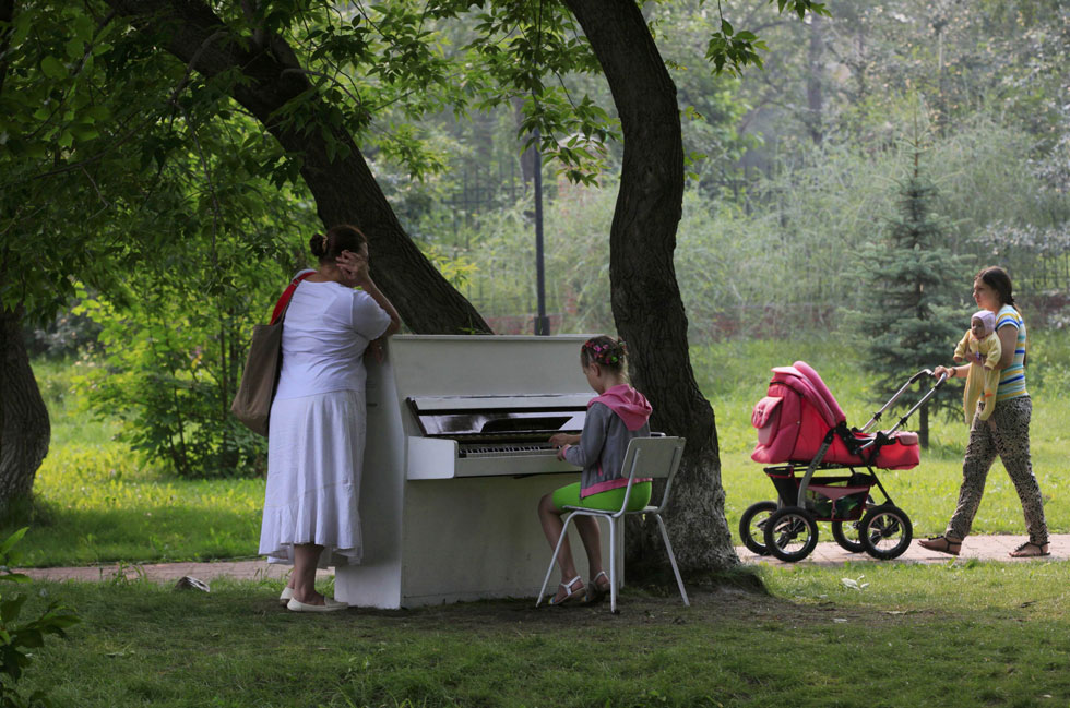 "A girl plays piano in the park in Russia's Siberian city of Krasnoyarsk, August 7, 2013. A group of young enthusiasts bought an old Soviet-made piano, adjusted it, painted white and placed in a park for free use by all visitors. The instrument is covered with a plastic foil at night and during rains. This is the group's first step in their project ""Free city entertainments"", local media said. REUTERS/Ilya Naymushin"