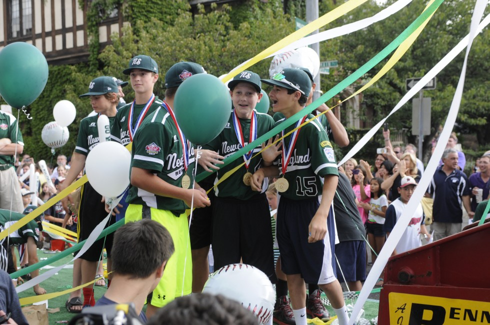 The Westport Little League team rides on the back of an open-air trailer along Main Street during the parade.
