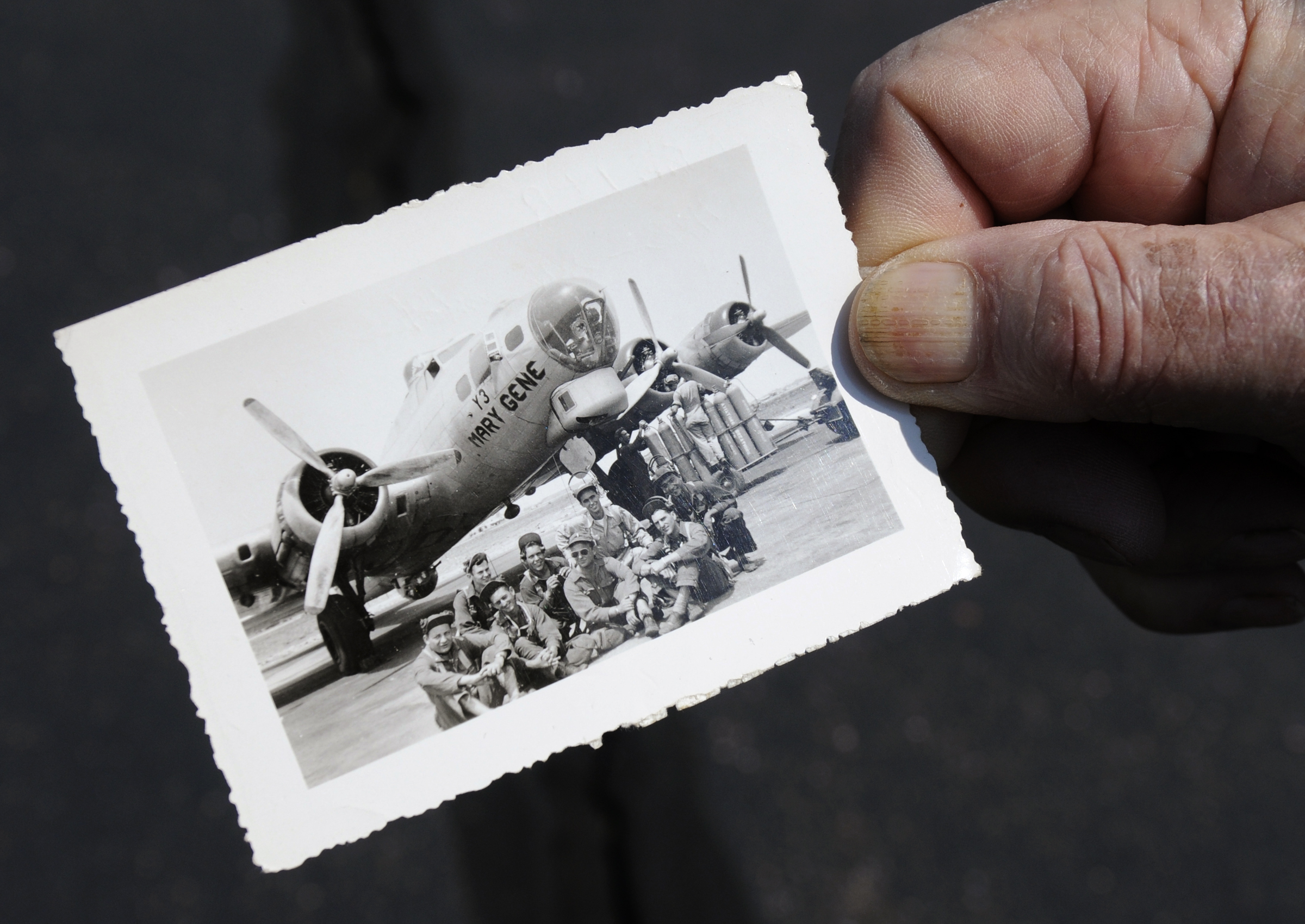 Ken Johnson holds a picture taken of himself and his crew in front of the aircraft he trained on before the war ended.