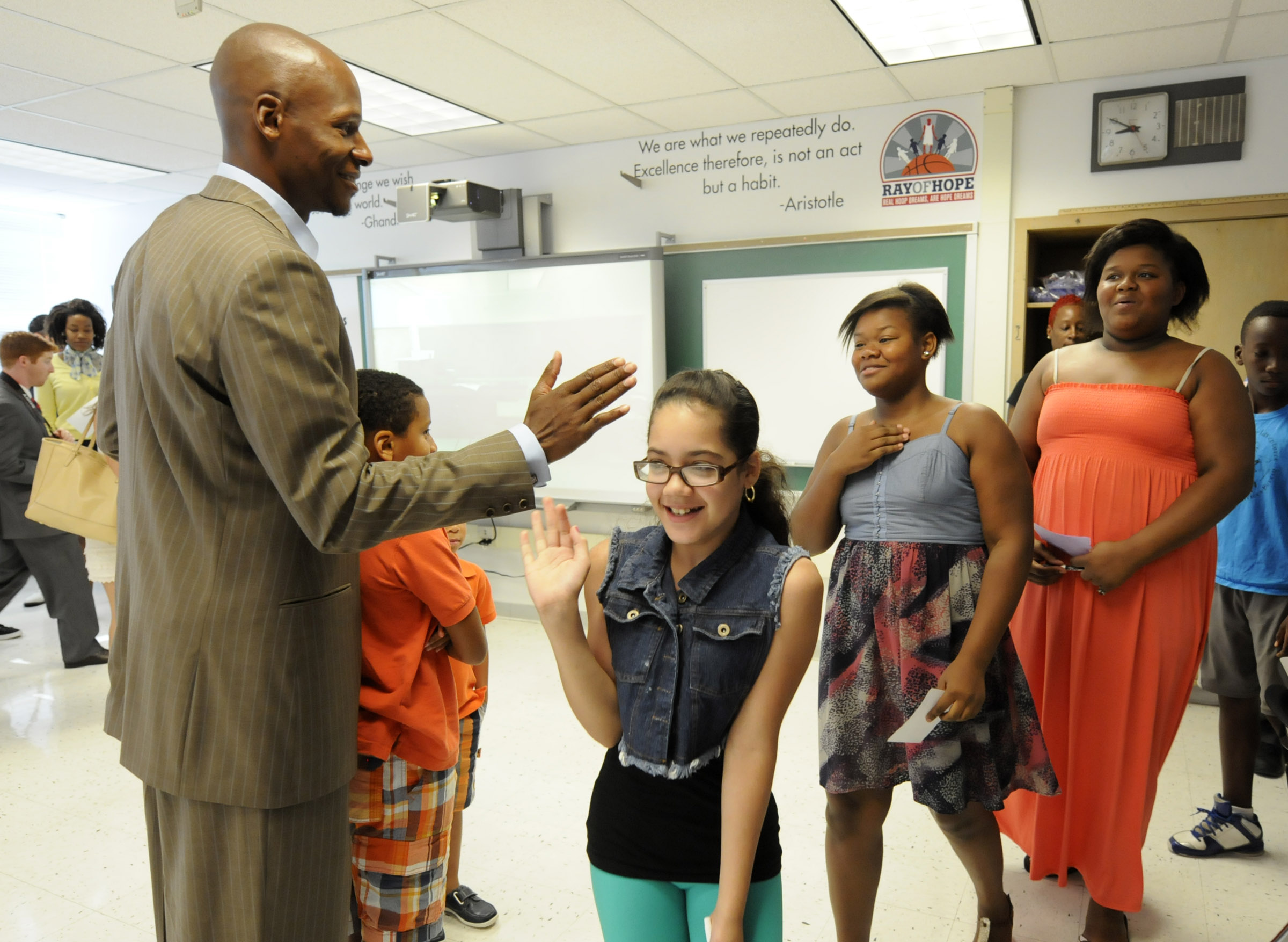Basketball star Ray Allen offers high fives to students filing into the Wish School's new computer lab funded by Allen's foundation Ray of Hope. The students are from left, Jadalin DeJesus, 11, and twin sister Shania Coleman and Amya Coleman.