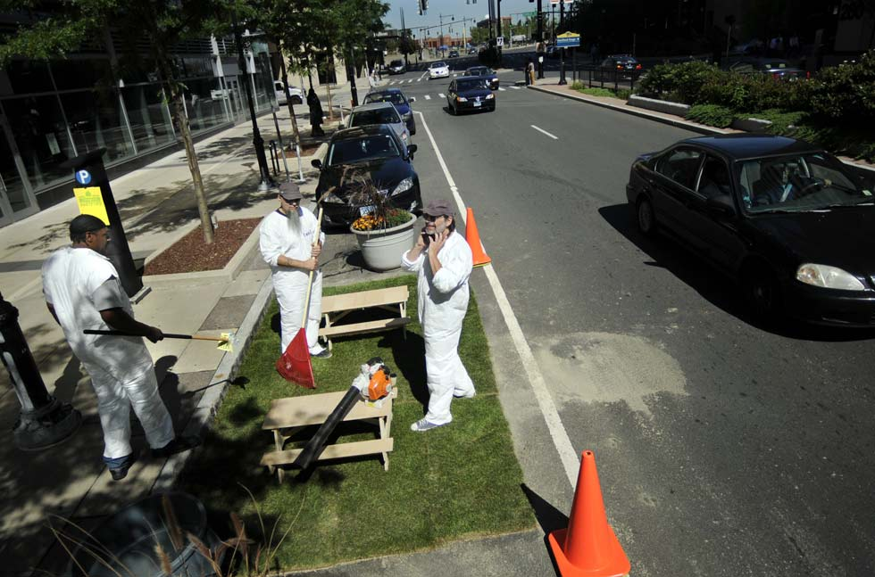 "Three artist friends claimed a parking spot on Trumbull Street in front of the XL Center and transformed it into a ""mini"" park with tiny picnic tables and sod. In photo, Gil Scullion of Middletown, right, prepares to use his power leaf blower to clean up the park while Michael Thomas of New Britain, left, picks up trash and David Borawski of Hartford, center,  waits to rake."