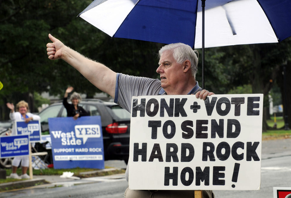 Residents  are voting whether they support or reject an $800 million casino proposal by Hard Rock International on the grounds of The Big E (Eastern States Exposition). I n background, a group in favor of the proposed casino waves to drivers.