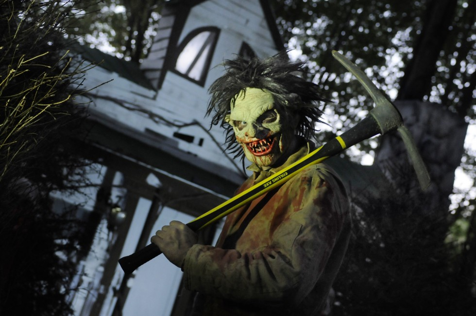 Owner/operator Eric Soltis, of Shelton, poses in front of the main house with one of the masks, and an ax actors will use during the tour to help scare their visitors.