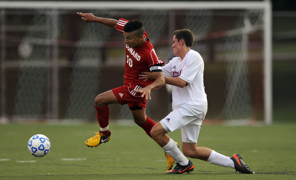 Matheus Souza of Conard battles with Kris Langevin of Berlin for a loose ball during the first half of their season opener at Sage Park in Berlin Tuesday evening. Berlin had a tough time keeping Souza in check as he scored 2 of Conard's goals as they defeated Berlin 4-2.
