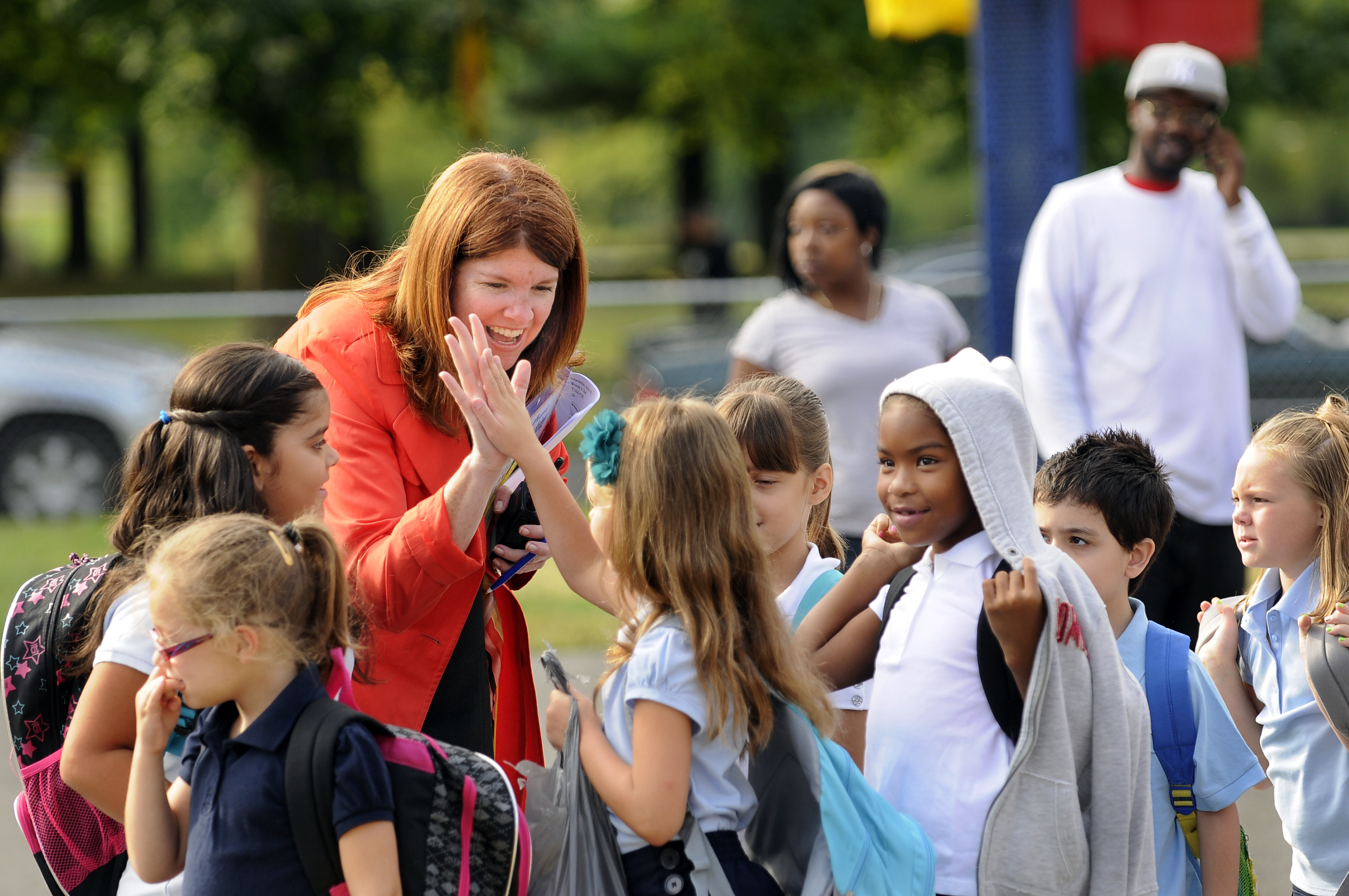 NEW BRITAIN 09/03/13 - Vance Village Elementary School principal Sarah Harris high fives a 2nd-grade student just before the start of the first day of school in New Britain.  Vance Village is a K-5 school with a student body of about 500. CLOE POISSON|cpoisson@courant.com