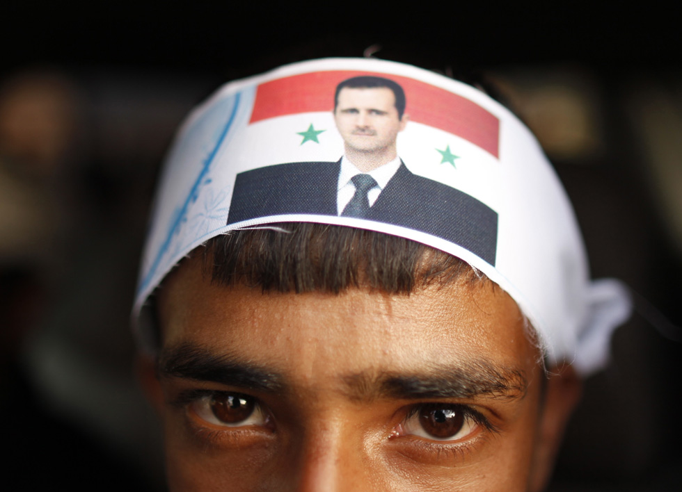 A protester loyal to the Shi'ite Muslim Al-Houthi group, also known as Ansarullah, wears a headband with a picture of Syria's President Bashar al-Assad, following a demonstration against potential strikes on the Syrian government.,  REUTERS/Khaled Abdullah