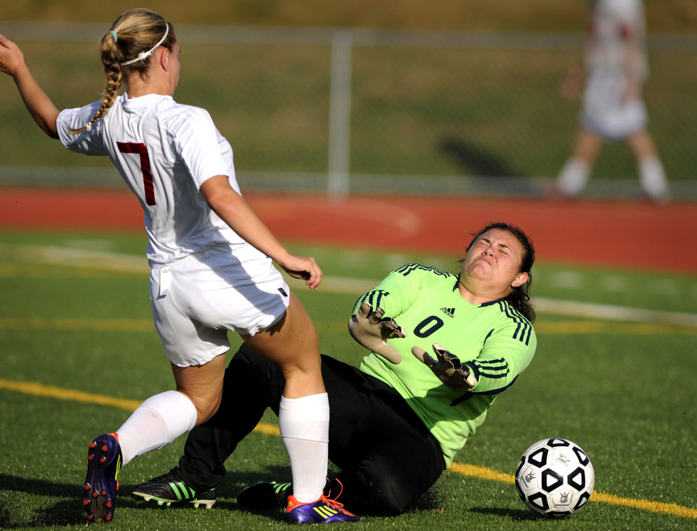 EO Smith's (7) Taylor Bisaillon, left, scores despite a valiant effort by Rocky Hill goalkeeper Marisa Carreira in the first half.