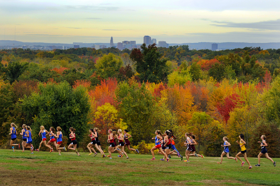 With the Hartford skyline and the fall foliage as a backdrop the varsity girls make their way across a field near the start of the race. — John Woike / Hartford Courant, Oct. 16, 2013