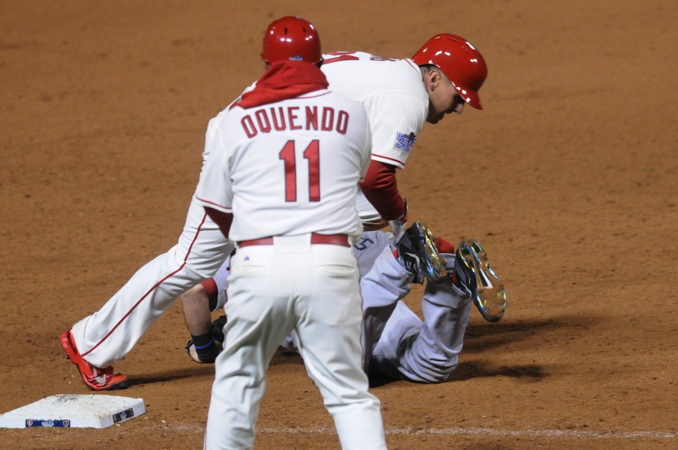 St. Louis Cardinals first baseman Allen Craig, 21, stumbles over Boston Red Sox third baseman Will Middlebrooks, 16, as he heads to the plate. The the Cardinals scored the winning run on the play when the umpire called obstruction by Middlebrooks.