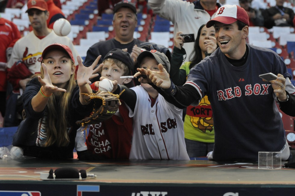Fans reach for a ball tossed to them from a Red Sox player as he left the field after pre game warm-ups. From  left, are. an unidentified girl, Hanks Edwards, 10, of Missouri, Yianni Georgacacos, 9, and his father, Aki, of Calgary.
