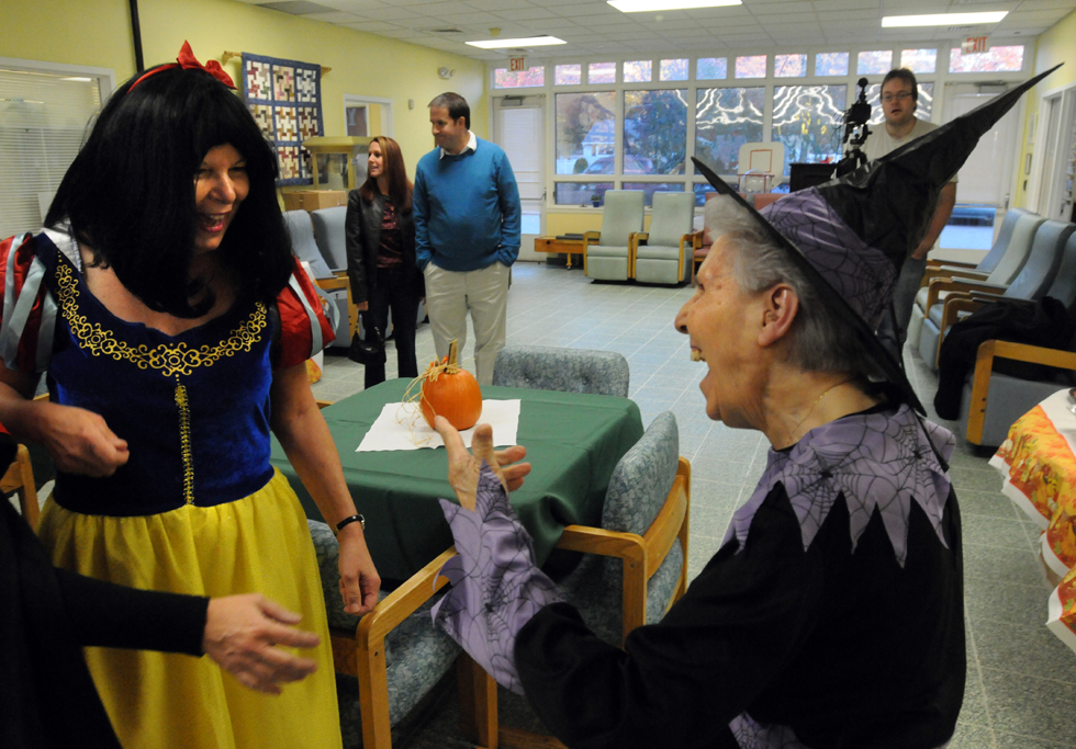 Celia Saracco, right, dressed as a witch, who lives at Mark Twain congregate living, Enfield, greets nurse's aide Joanne Alphonse (dressed as Snow White) at the party as Enfield's Adult Day Center celebrated 20 years in service Thursday. In honor of the celebration, Dorothy Allen, the co-founder of the Adult Day Center, attended.