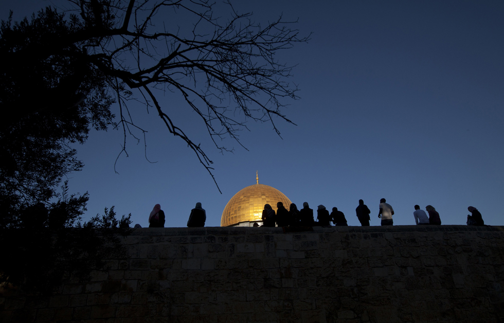 "Palestinian Muslim worshipers sit on a wall in front of the golden dome inside the Al-Aqsa Mosque compound, Islam's third holiest shrine, in Jerusalems old city, following morning prayers on the Muslim holiday of Eid al-Adha or ""The Feast of Sacrifice."" October 15, 2013. AHMAD GHARABLI/AFP/Getty Images"