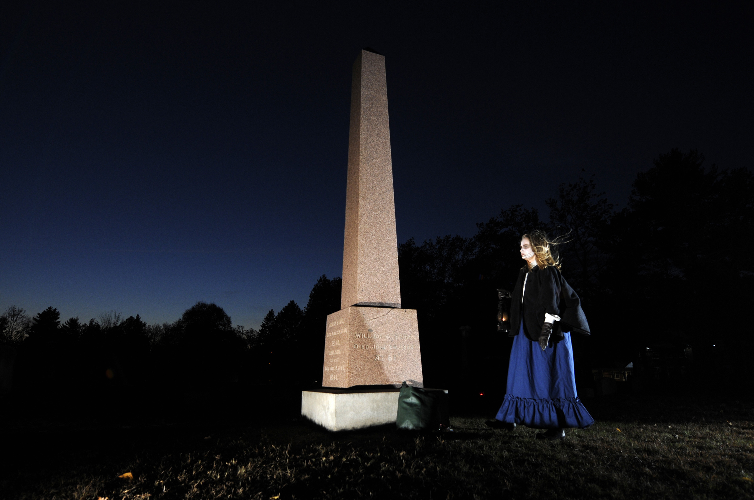 Katie Smith, of West Hartford waits to take her cue during West Hartford Hauntings at North Cemetery, a nighttime tour of the West Hartford cemetery featuring actors and local scary stories. The lantern lit tour is sponsored by the Noah Webster House.
