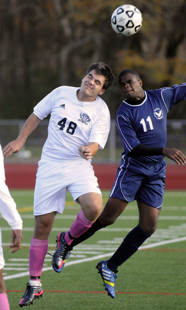 HARTFORD--Fermi's Matt Stroiney, #48, left, and Hartford Public's Nushawn Clarke, #11, right, go head to head during Hartford Public at Fermi boys high school soccer game Tuesday. The score was tied one to one in double overtime.  (RICK HARTFORD|rhartford@courant.com)