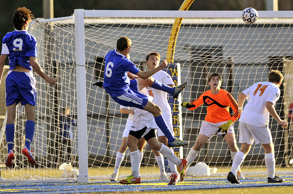 2013.11.16 - Waterbury, CT - Glastonbury's Tyler Peterson (second from left) falls backward after heading the ball for a goal in the Class LL Championship against Ridgefield. The game ended in a 1-1 tie with the two teams being named co-champions. Photograph by Mark Mirko | mmirko@courant.com