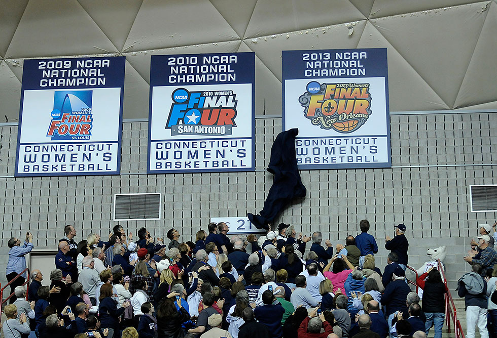 Jonathan the Husky Dog unveils the 8th national championship banner before the No.1 UConn women defeated No. 3 Stanford 76-57 at Gampel Pavilion Monday night.